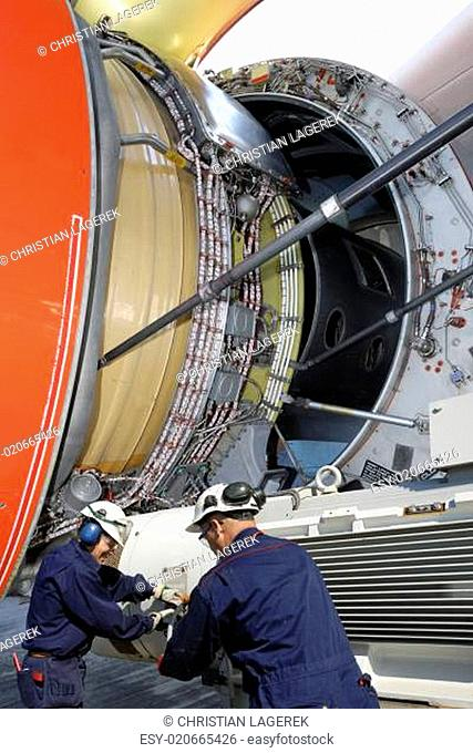 airplane mechanics calibrating a jet engine