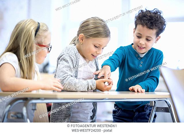 Three pupils in class stroking mouse