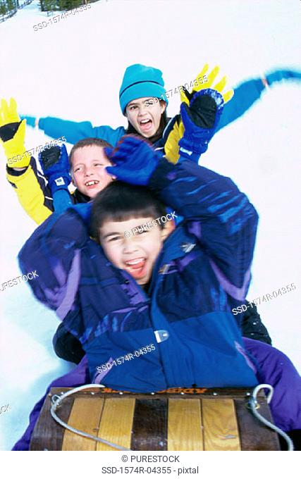 Two boys and a girl riding a sled