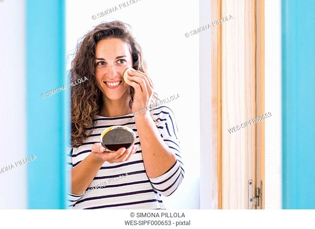 Young woman at home applying face powder