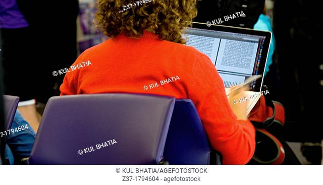 A young woman working with a laptop computer, Ontario, Canada  An e-book or other digital file is visible on the computer screen  Blurred hand suggests writing...