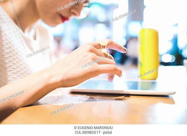 Woman at table using digital tablet, Milan, Italy
