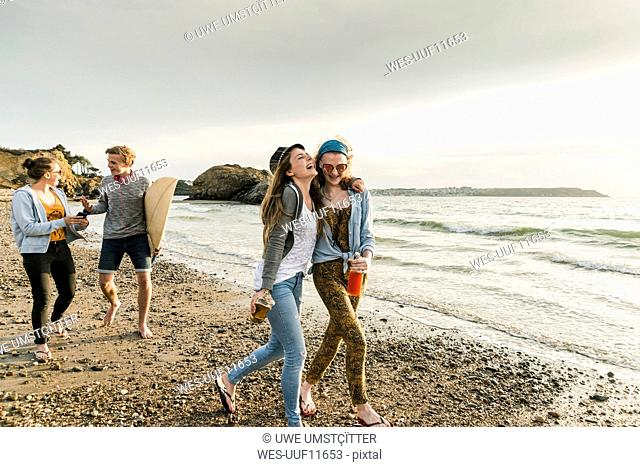Happy friends with surfboard and drinks walking on stony beach