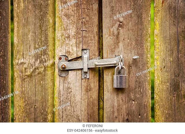 Image of wooden gate with metal hinge and padlock