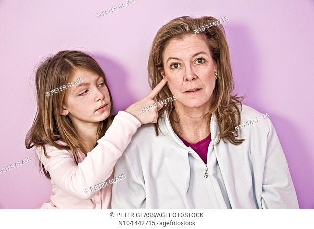 Preteen girl sticking her finger in her mother's ear