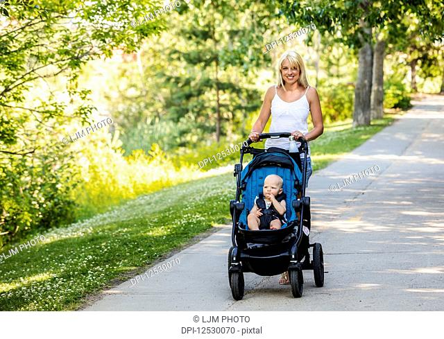 A beautiful young mother taking her baby daughter out for a walk using a stroller in a park with a lake on a warm sunny day; Edmonton, Alberta, Canada