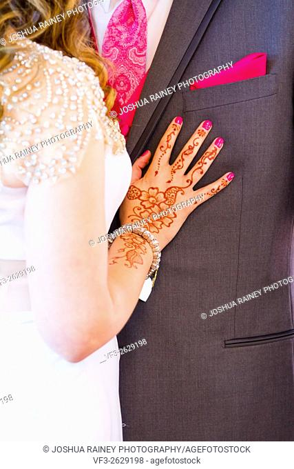Wedding tattoos of henna on an Indian bride at a Catholic church next to her groom after their ceremony