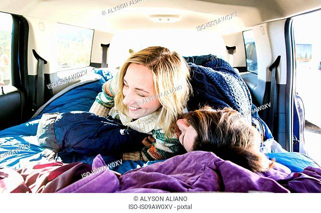 Young couple lying down in recreational vehicle, fooling around, laughing
