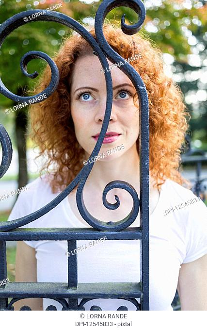 Portrait of a woman with red, curly hair and bright blue eyes standing behind a wrought iron gate and looking up; Burnaby, British Columbia, Canada