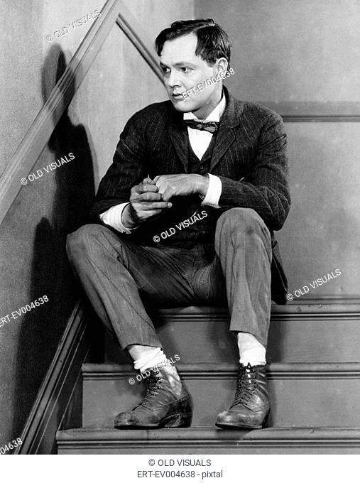 Portrait of troubled man sitting on stairs All persons depicted are not longer living and no estate exists Supplier warranties that there will be no model...