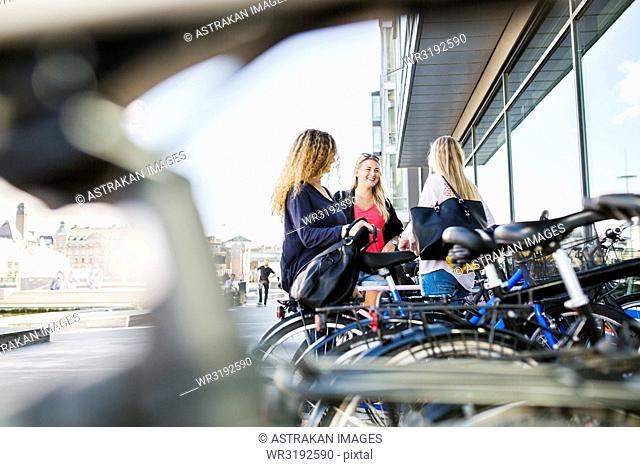 Three young women standing by bicycles