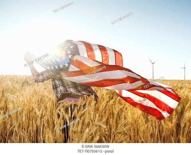 Girl 12-13 flying american flag in wheat field