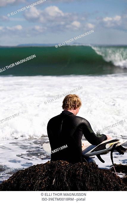 Surfer sitting on seaweed in waves