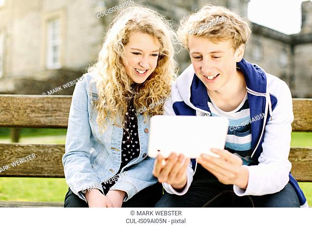 Teenage brother and sister looking at digital tablet on bench