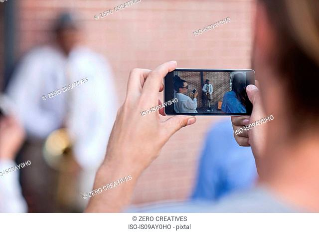 Pedestrian taking photograph of street musician, using smart phone