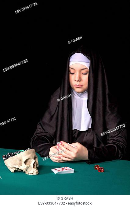 Nun playing cards at green poker table hands covering his cards isolated on a black background