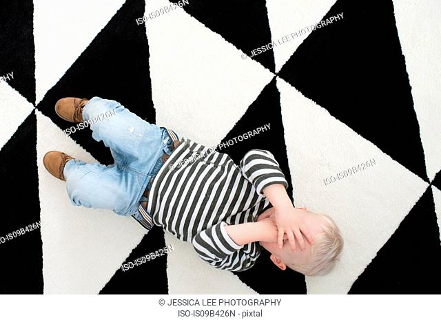 Young boy lying on floor, covering eyes, elevated view