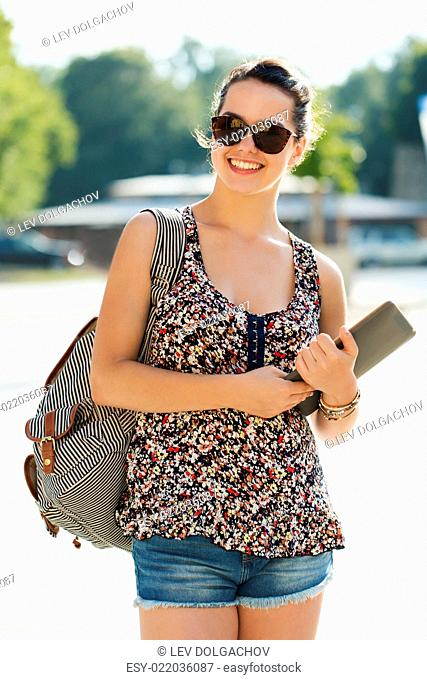 tourism, travel, summer holidays and people concept - happy teenage girl with tablet pc computer and backpack in city