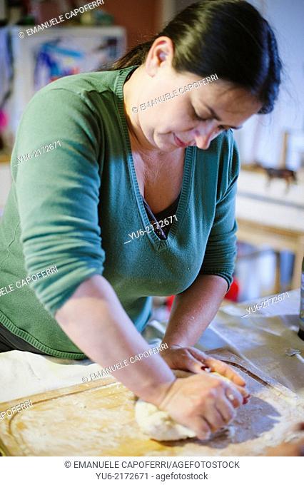 Woman kneads the flour to make a cake