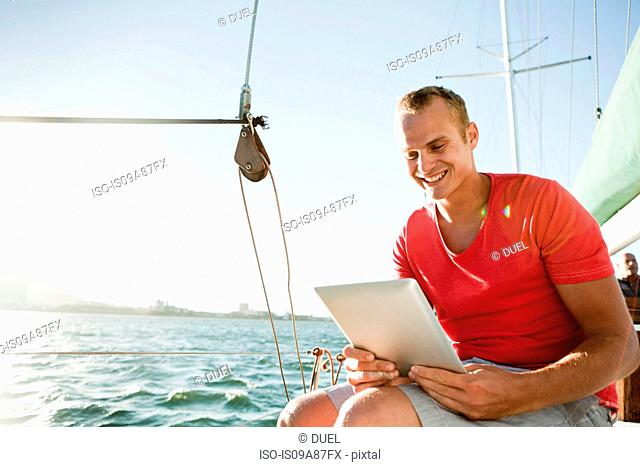 Young man on yacht using digital tablet