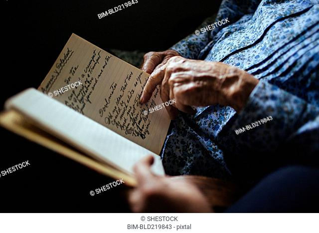 Older woman reading handwriting to granddaughter