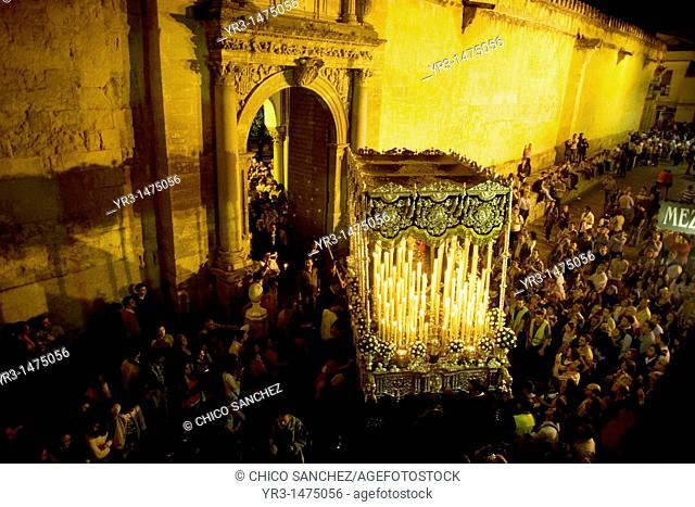 A throne displaying a Virgin Mary sculpture is carried through a doorway of the Mosque-Cathedral of Cordoba during an Easter Holy Week procession in Cordoba