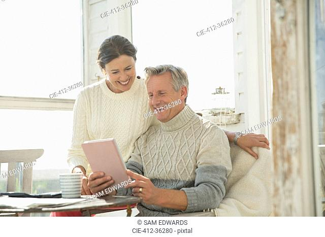 Smiling mature couple using digital tablet at table on sunny sun porch