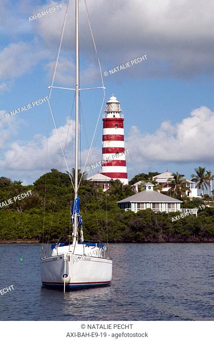 Boat sailing in front of a striped lighthouse. Abaco Islands, Elbow Cay, Hope Town, Bahamas