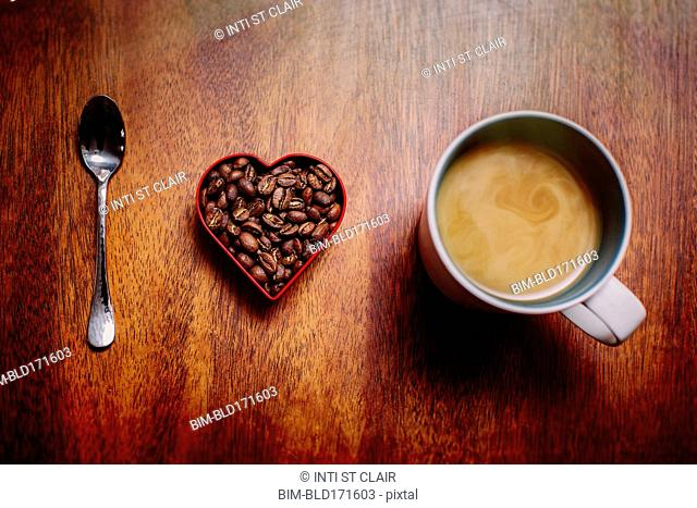Spoon, beans and cup of coffee on counter