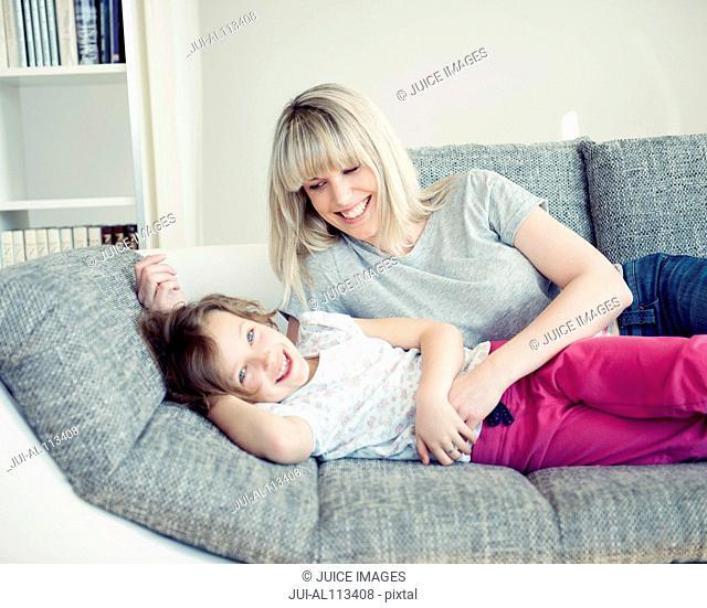 Young girl and mother lying on sofa