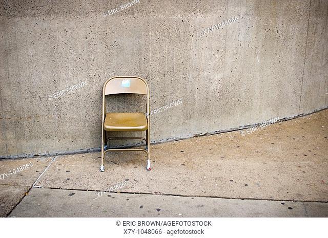 A folding chair sits against a wall