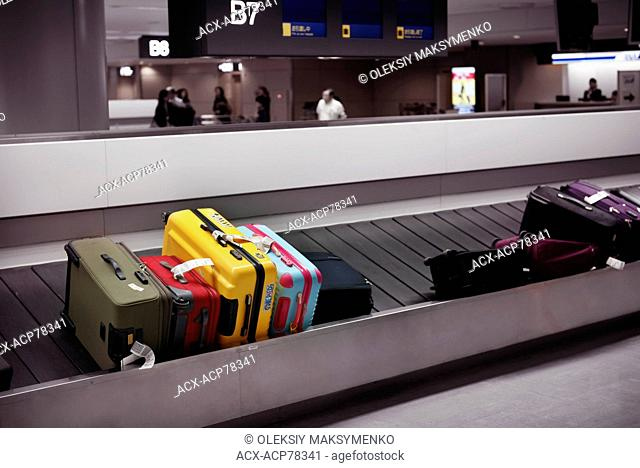 Colorful suitcases on airport baggage claim conveyor carousel, Narita International Airport, Japan