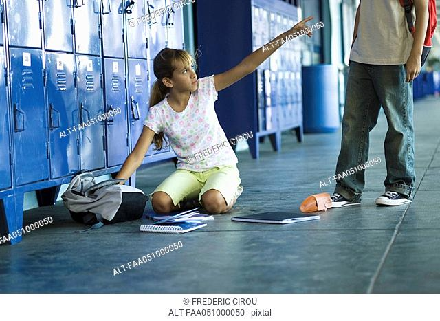 Female junior high student sitting on floor pointing angrily up at boy standing over her