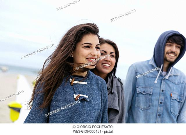 Italy, Rimini, portrait of three happy friends on beach out of season