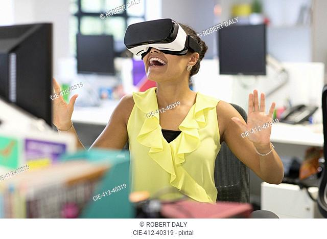 Enthusiastic businesswoman using virtual reality simulator glasses in office