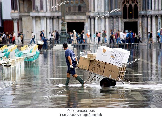 Aqua Alta High Water flooding in St Marks Square with a delivery man pulling a trolley of goods through the water with St Marks Basilica at the end of the...