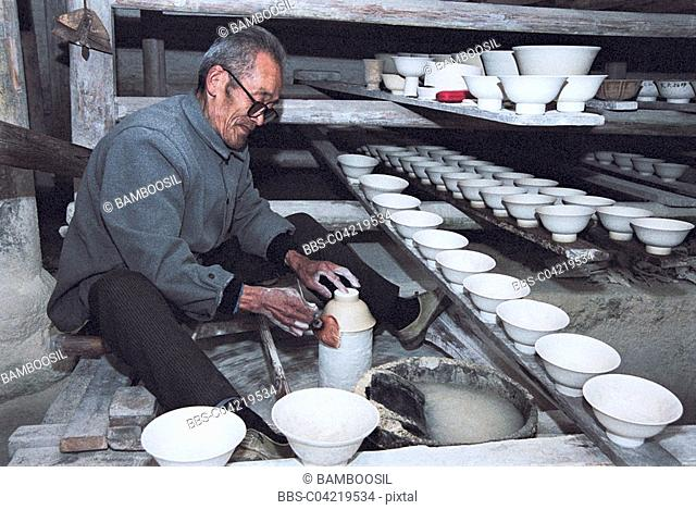 Senior man manufacturing ceramics in ancient kiln workshop, Jingde Town, Jiangxi Province of People's Republic of China