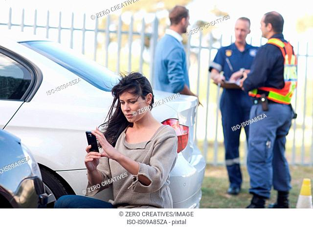 Woman photographing damage on her car at car accident scene