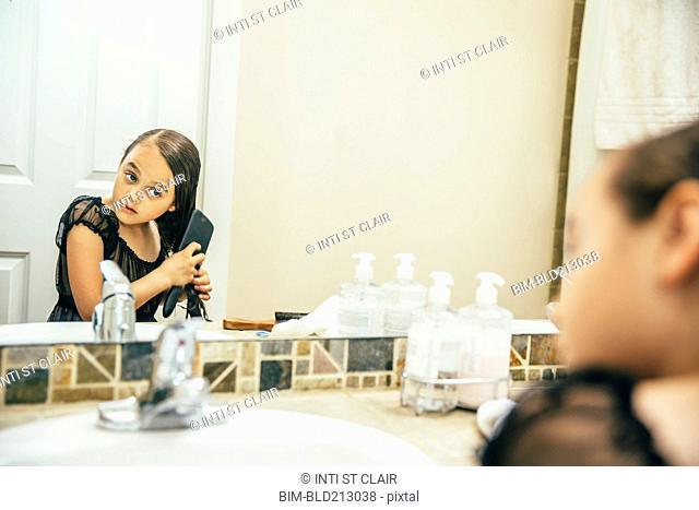 Mixed race girl brushing hair in bathroom