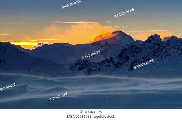 Europe, Italy, Lombardy, Sondrio, Wind puffs in the summit of mountains of Alta Valtellina at sunset