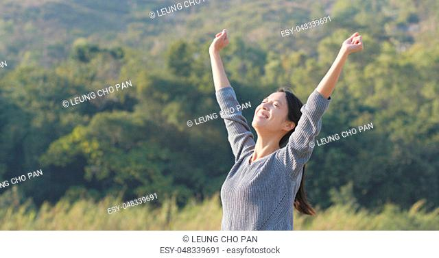 Excited woman raising hand up at outdoor