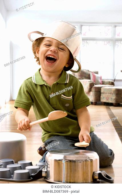 Mixed race boy beating on kitchen pots