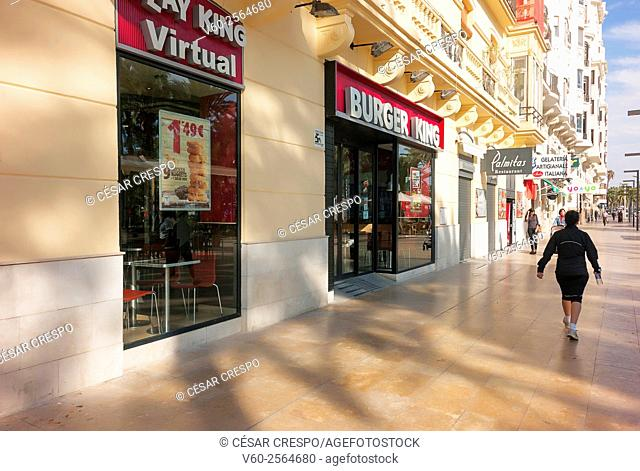 -Woman passing front Fast Food Shoppings- Alicante Spain
