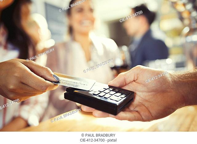 Woman with credit card paying bartender with contactless payment at bar