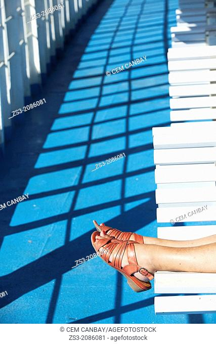 Woman's feet with red pedicured toes on the seat of a deck in ferry, Milos, Cyclades Islands, Greek Islands, Greece, Europe