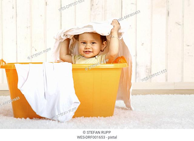 Baby girl sitting in a laundry basket