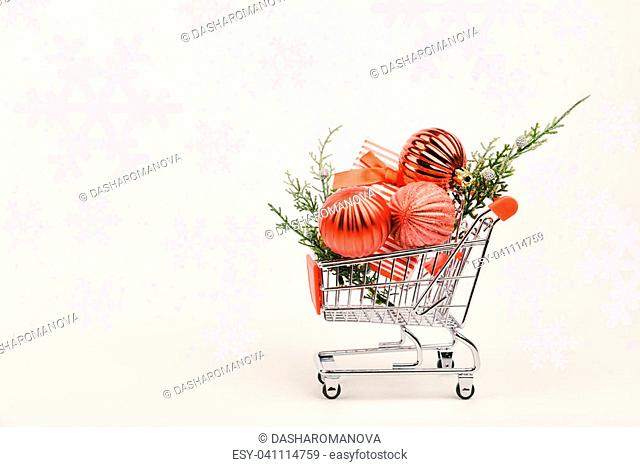 Supermarket cart with fir-tree branch and red bauble isolated on white background. On-line internet buying concept