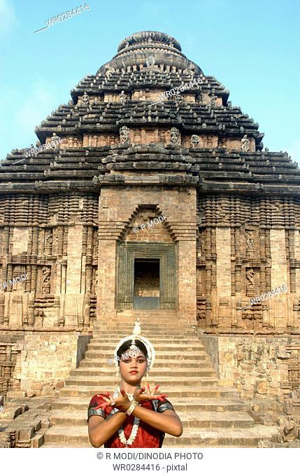 Dancer performing classical traditional odissi dance in front of Konarak Sun temple , Konarak , Orissa , India MR 736C