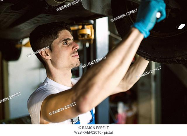 Mechanic working on the underbody of a car in a workshop
