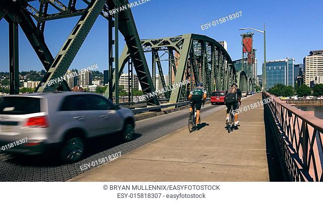 Cyclists and automobiles cross the Hawthorne Bridge heading into Portland, Oregon